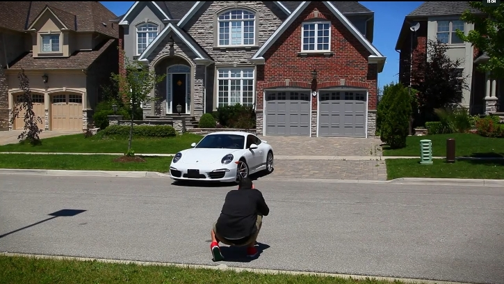 photographer taking a picture of a new, white Porsche positioned in the driveway of an upscale home