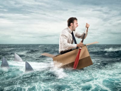 image of a man paddling a cardboard box, looking very anxious, followed by three sharks