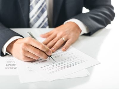 Man in suit signing dental marketing contract quote paperwork.