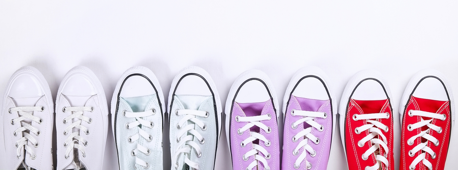 Four pairs of converse sneakers in different colors as an example of template based dental websites.