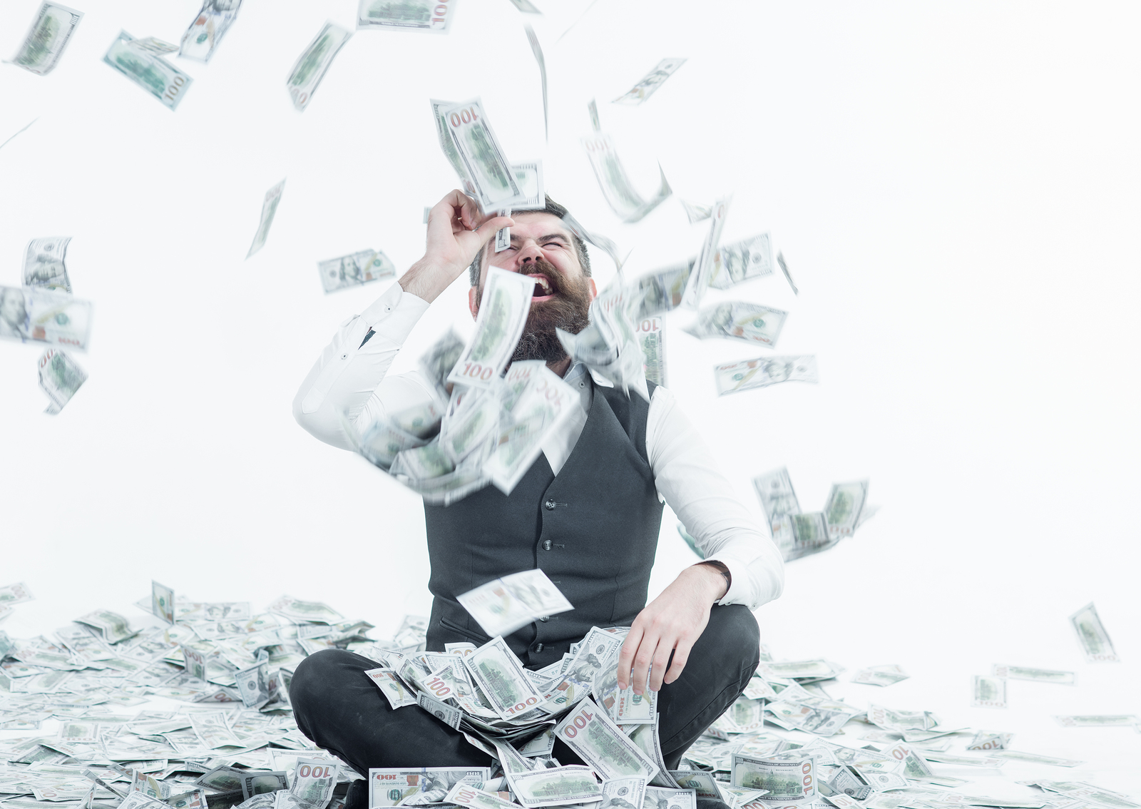 Man in business attire sitting down and laughing in greed about dental web agencies among a shower of hundred dollar bills