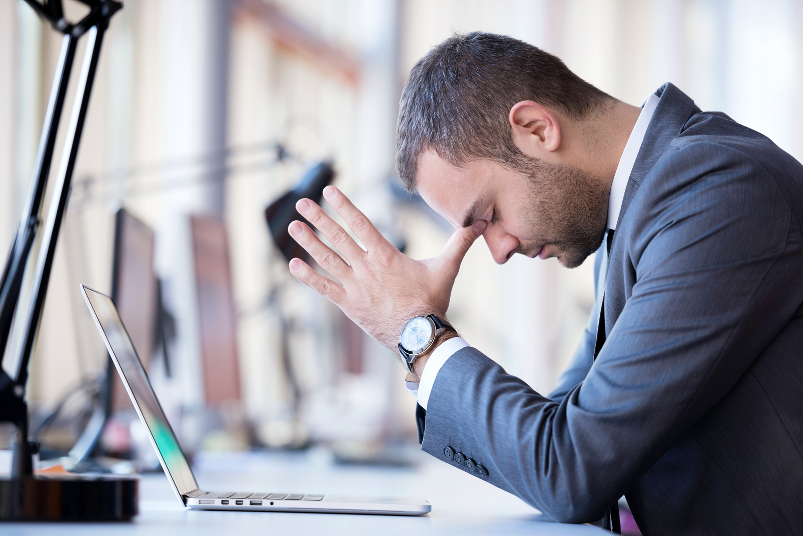 Man in business suit with closed eyes and head in hands in front of laptop worried about his dental website agency.