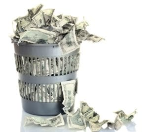 A photo of a wastebasket full of crumpled money to illustrate money wasted on poor SEO strategies